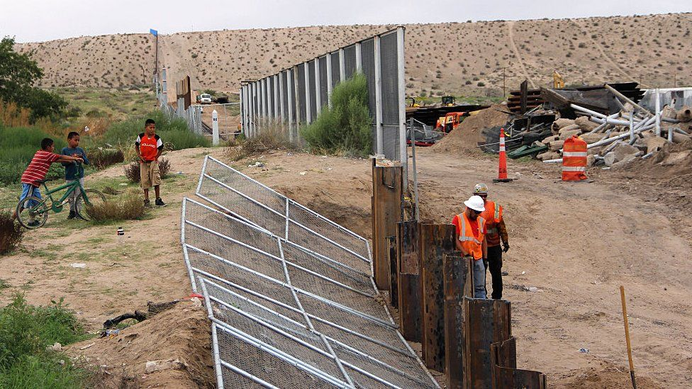 Construction workers assemble a portion of a border wall between the US and Mexico.
