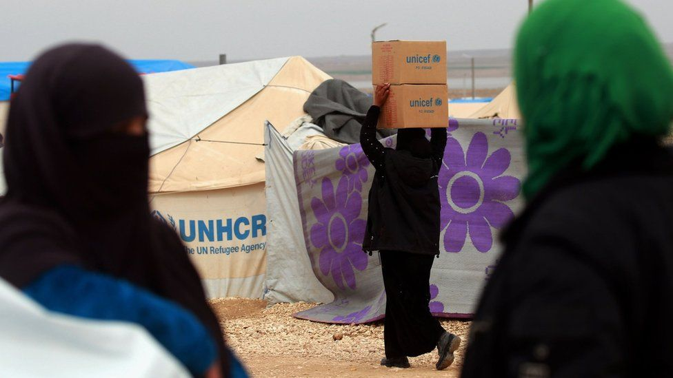 A woman carries boxes of humanitarian aid supplied by Unicef at a refugee camp in Syria's north-eastern Hassakeh province on February 26, 2018