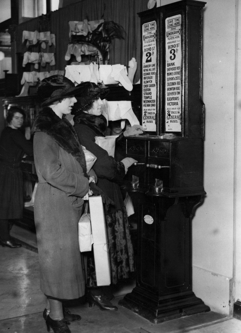 Women using an underground ticket machine located inside Selfridge's in 1923