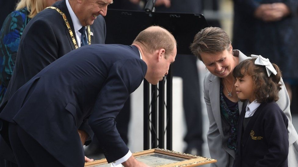 The Duke of Cambridge receives a gift from a young girl
