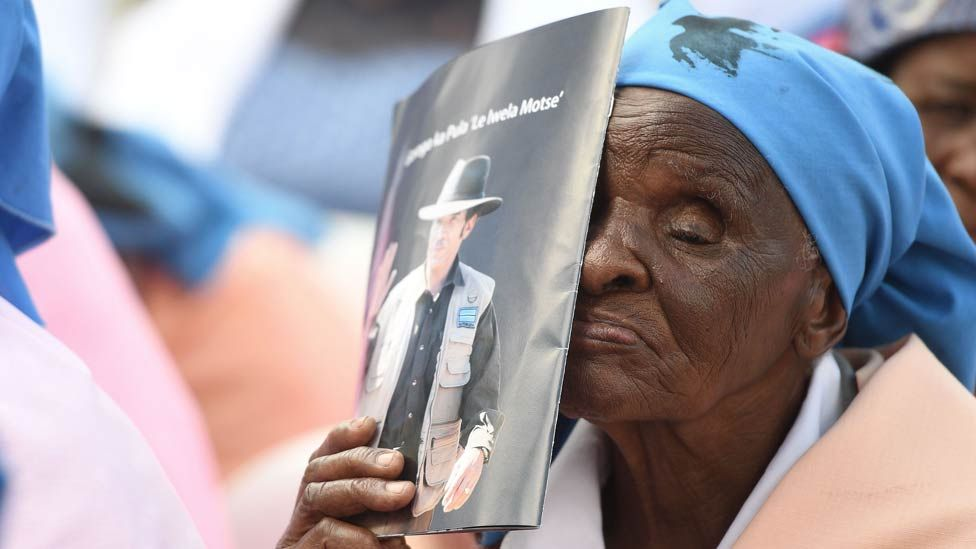 A woman holds a brochure carrying a portrait of Botswana's President as he arrives at a rally in his village on March 27, 2018