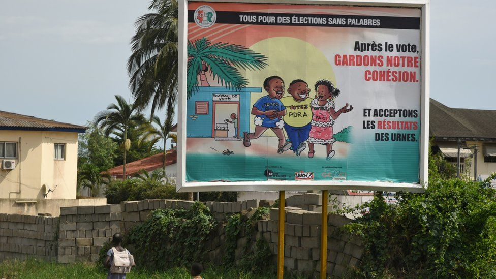 """Children pass an Independent Electoral Commission (CEI) poster reading """"All for an election without debate"""", """"After the voting, keep our cohesion"""" and """"accept the results of the ballot box"""" in Abidjan"""