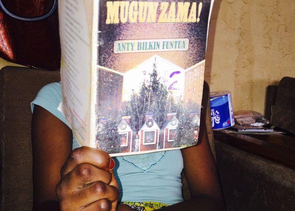 Someone reading a Hausa romance novel