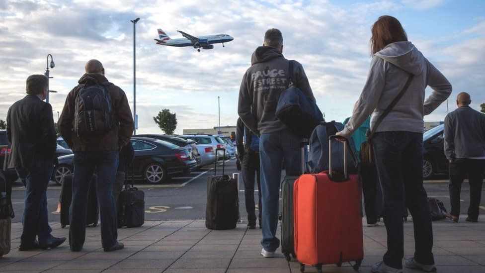 Passengers wait for a shuttle bus at Heathrow