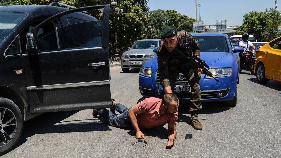 A Turkish police officer restrains a man on the ground during an operation in front of the Ankara courthouse - 18 July 2016.