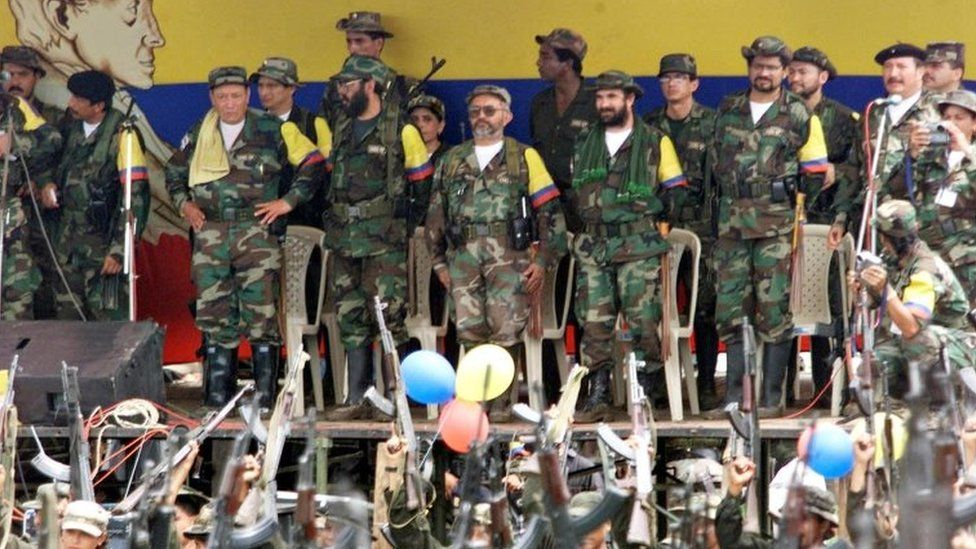 """Colombian leftist commanders (L to R) Manuel Marulanda, known as """"sureshot"""", Alfonso Cano, peace negociator Raul Reyes, Timochenko, Ivan Marquez and Jorge Briceno, all members of the general secretariat of the Armed Revolutionary Forces of Colombia (FARC), watch a parade of armed fighters at a camp in Villa Colombia near San Vicente del Caguan, Colombia, April 29, 2000"""