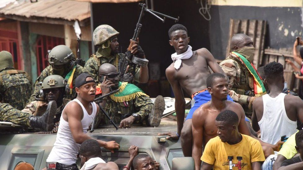 People celebrate in the streets with members of Guinea's armed forces after the arrest of Guinea's president, Alpha Conde