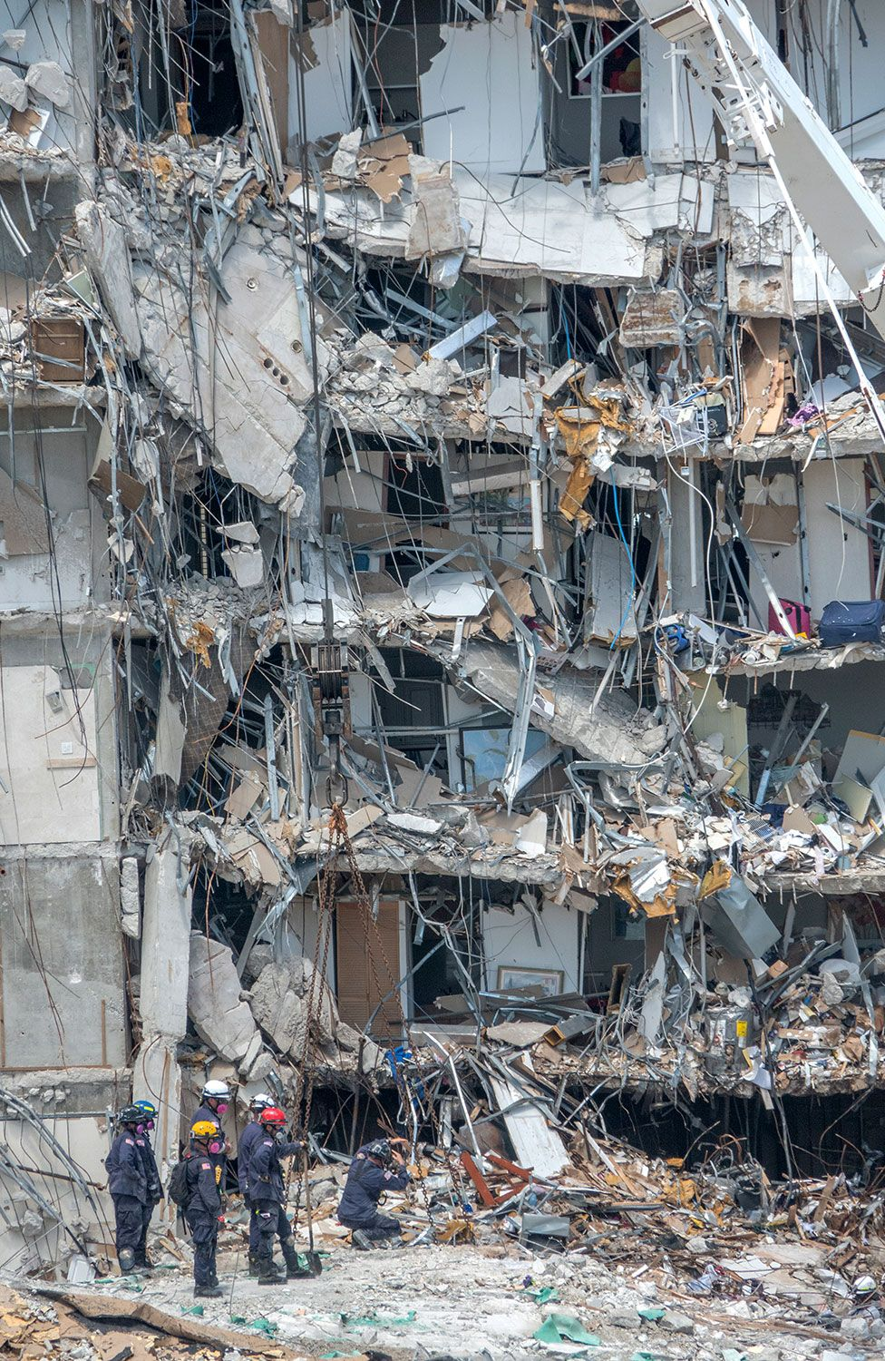 Rescue teams stand amid rubble of collapse building