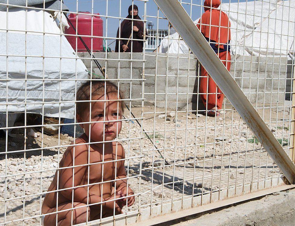 Criança agachada atrás de uma cerca de metal