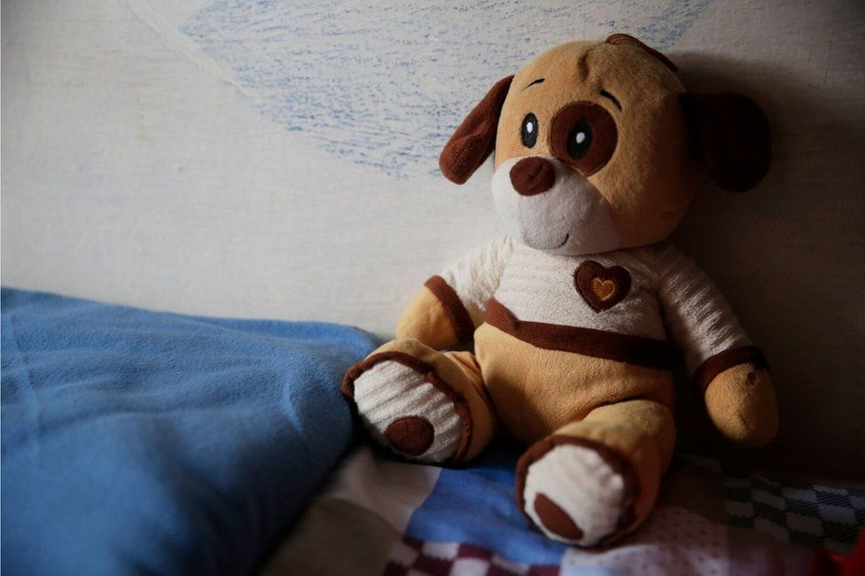 A cuddly toy sits on a bed in Punta de Rieles