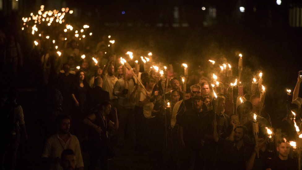 Neo-Nazis, alt-right, and white supremacists brandish torches during a night-time march