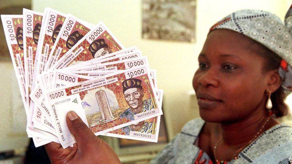 A woman displays several 10,000 CFA