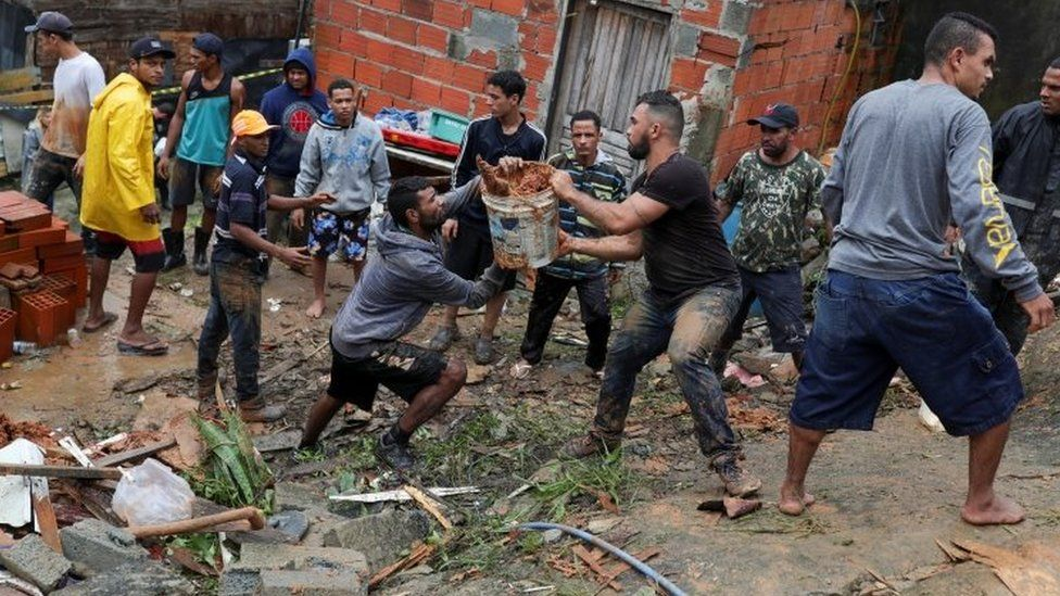 Residents in Guarujá clear the mud at the side of a landslide. Photo: 3 March 2020