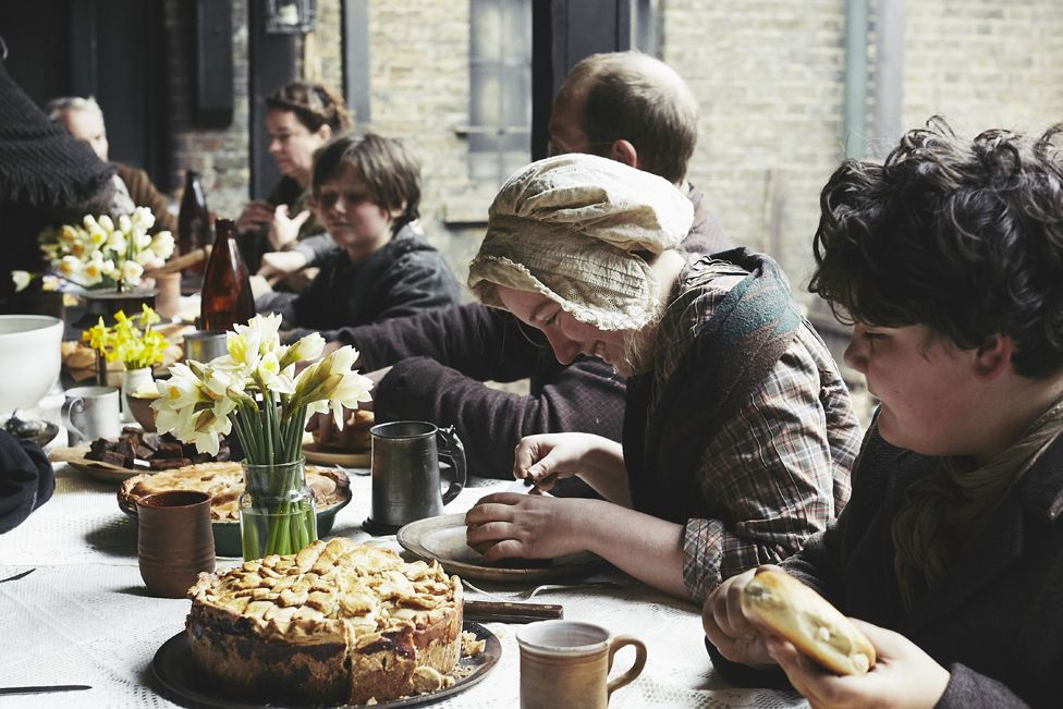 People dressed as Victorians having a Victorian-style meal