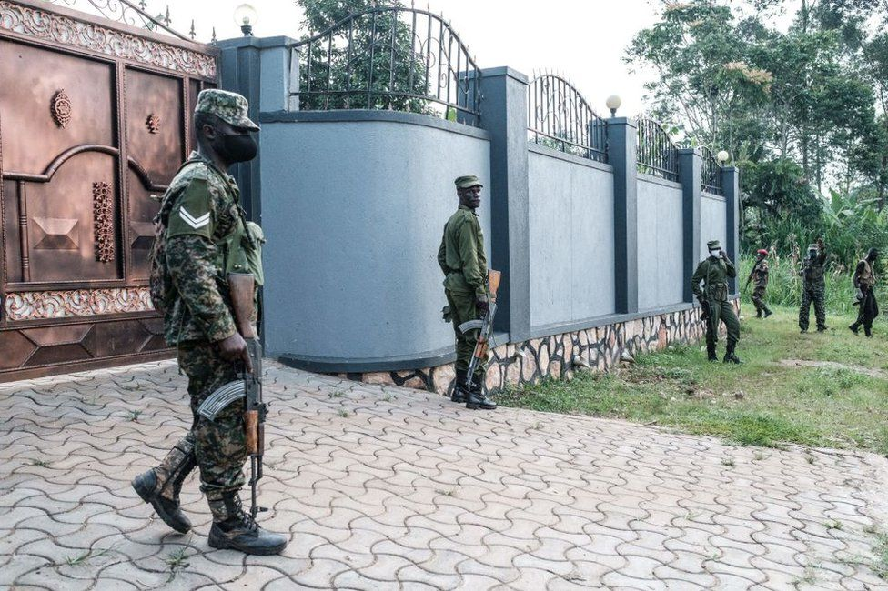 Soldiers stand next to a wall of the neighbours of presidential candidate Robert Kyagulanyi, also known as Bobi Wine, in Magere, Uganda, on January 15, 2021