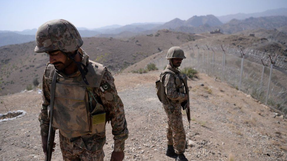 Pakistani soldiers patrol next to a newly fenced border fencing along Afghan border at Kitton Orchard Post in Pakistan's North Waziristan tribal agency on October 18, 2017