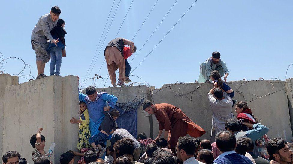 People climb the boundary wall of Hamid Karzai International Airport