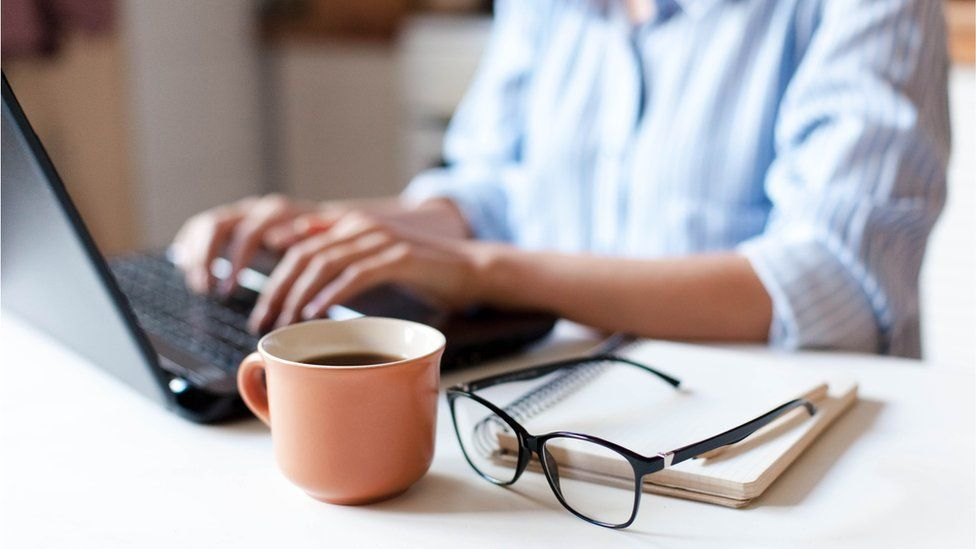 Woman typing on laptop with coffee mug