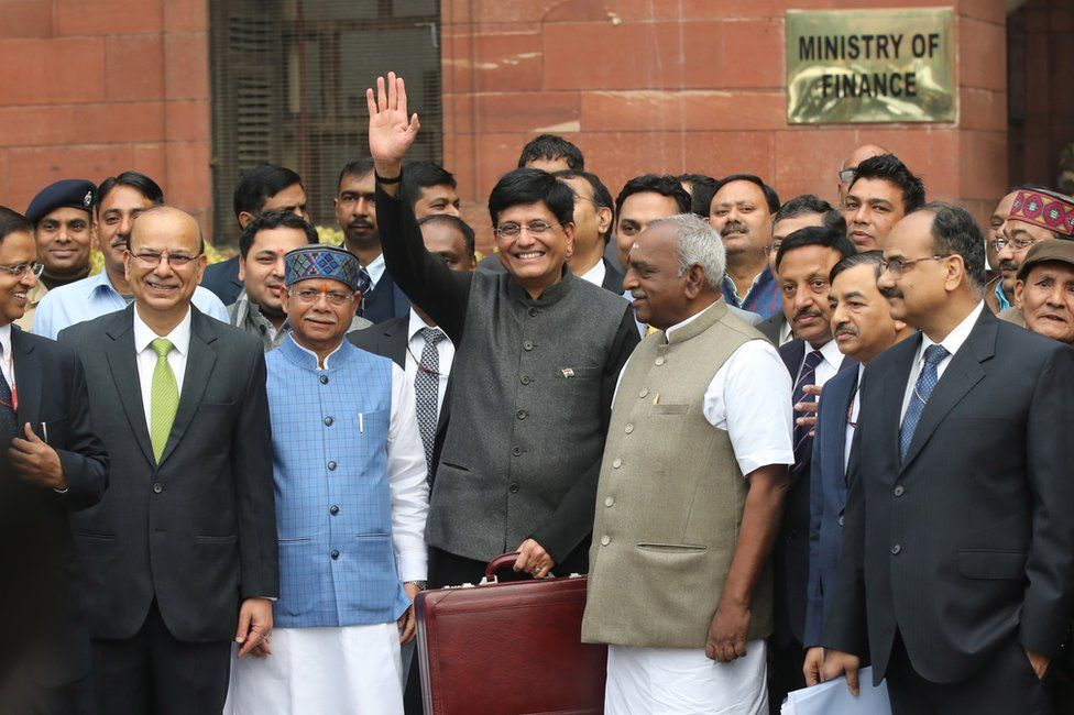 Indian Finance Minister Piyush Goyal (C) holds his briefcase, containing the Union Budget documents, as he poses for photos outside the Ministry of Finance for the Parliament House to present the 2019-20 General Budget in New Delhi, India.