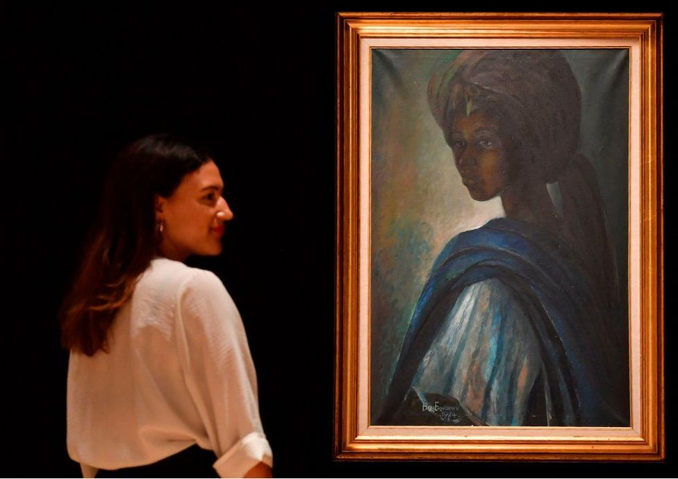 An employee poses with a work of art by Nigerian painter and sculptor Ben Enwonwu entitled 'Tutu' expected to realise 200,000-300,000 GBP (278000-417,000 USD) at auction in Bonhams auction house London on February 7, 2018. Tutu, a recently rediscovered portrait of the Ife royal princess Adetutu Ademiluyi painted in 1974 by the Nigerian artist Ben Enwonwu, leads Bonhams Africa Now sale in London on February 28. The painting, one of a series of three versions, once thought lost came to light after having gone unseen for decades in a north London flat. The whereabouts of the other two versions remains a mystery.