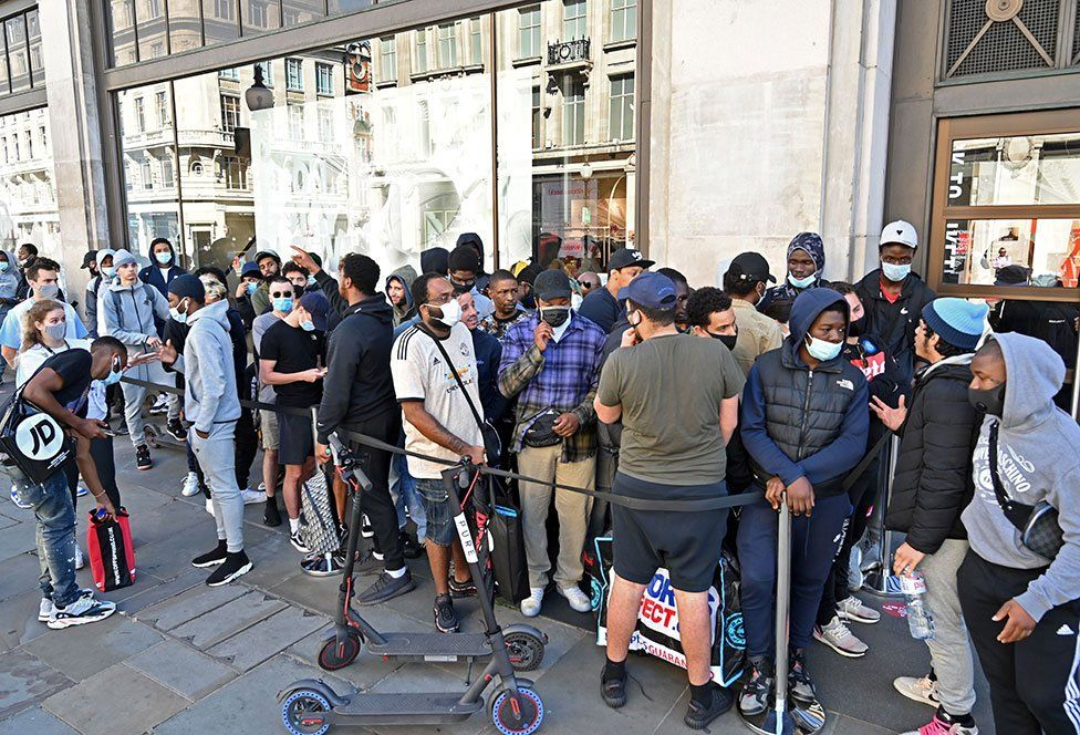 A group of shoppers queue outside a Nike store in London