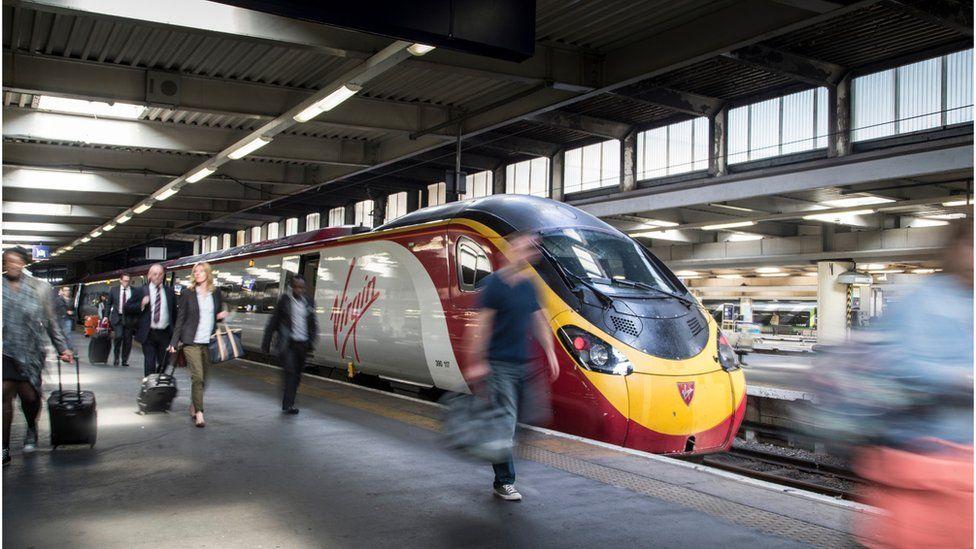 People disembark from a Virgin Train
