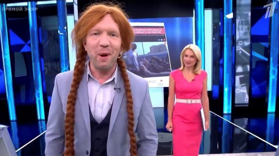 Russian TV presenter wearing a wig, smiling
