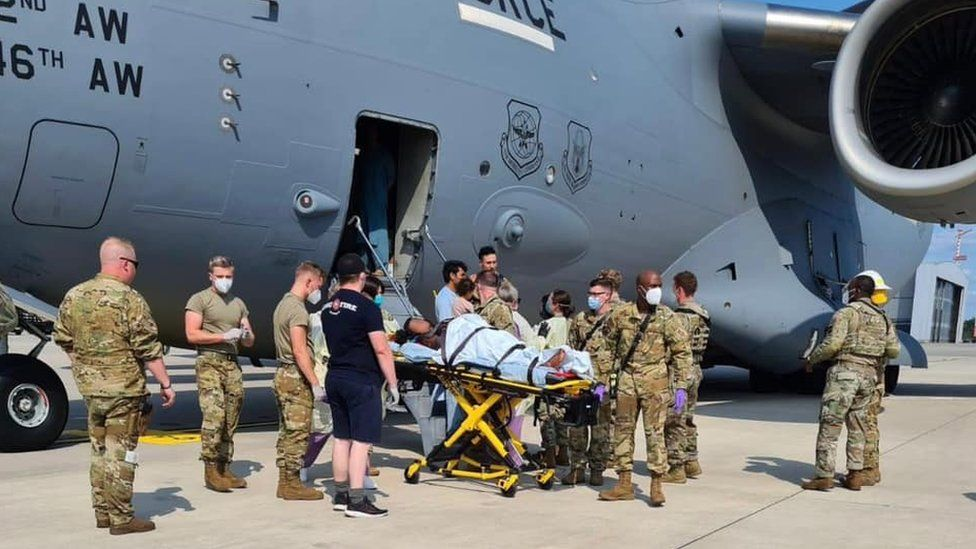 US forces take a mother and new born baby for medical attention after the women gave birth on an evacuation flight from Afghanistan