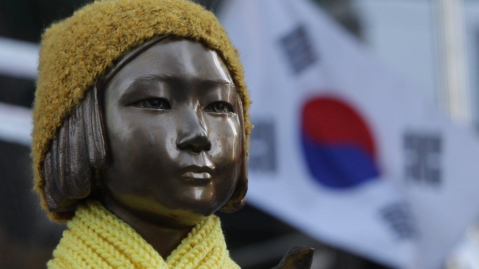 "A statue of a girl symbolising the issue of ""comfort women"" in front of the Japanese Embassy on December 28, 2015 in Seoul, South Korea"