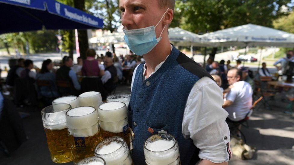 A server wearing a face mask carries mugs during a barrel tapping at a beer garden near Theresienwiese in Munich, September 2020