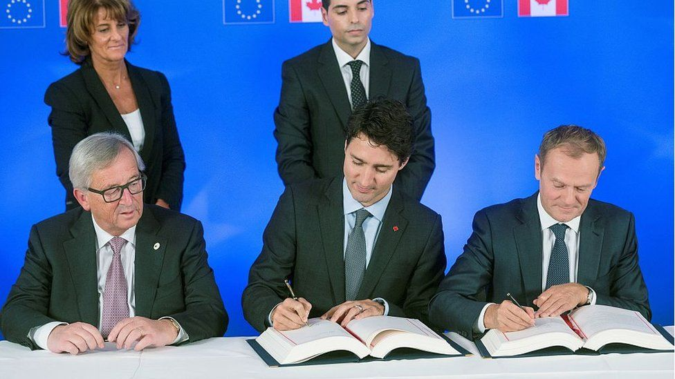 President of the European Commission Jean-Claude Juncker looks on as Canada's Prime Minister Justin Trudeau (C) and European Council President Donald Tusk sign the Comprehensive Economic and Trade Agreement