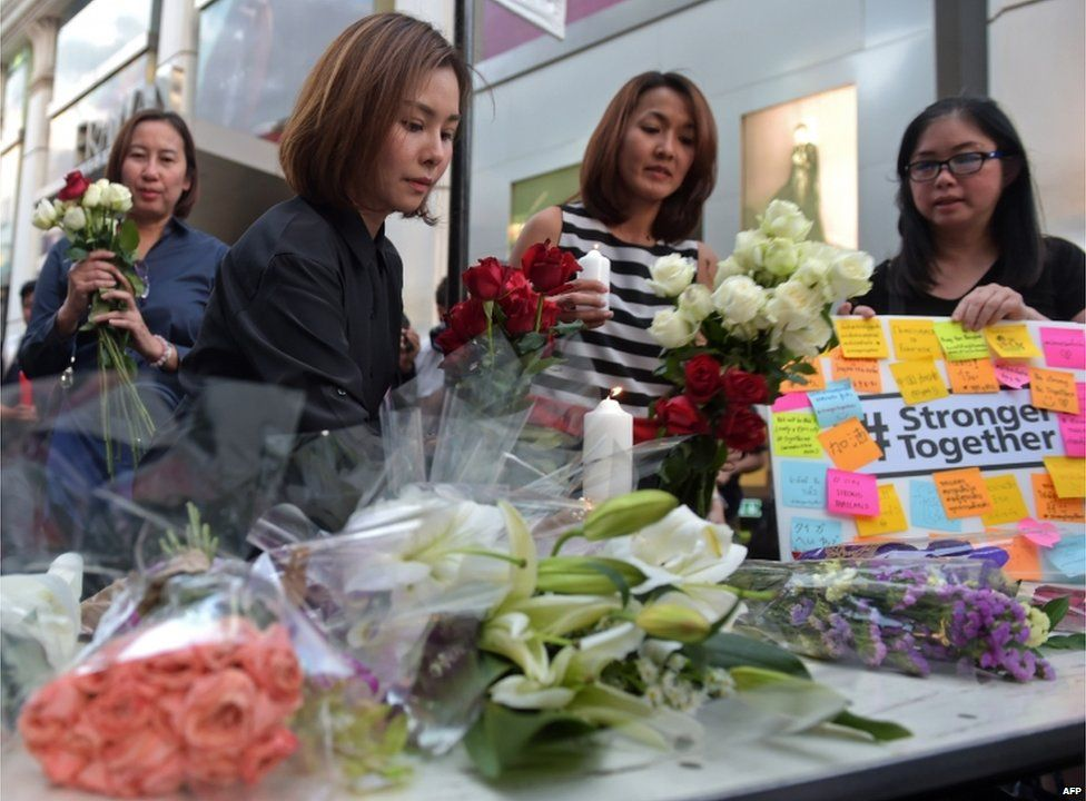 Thai office workers lay flowers for victims killed in a bomb blast outside a religious shrine in Bangkok on 18 August 2015