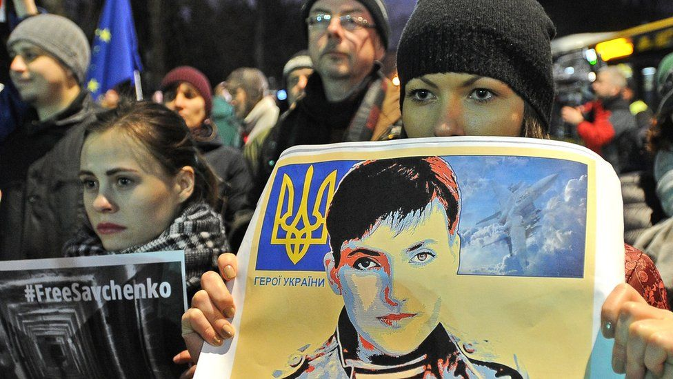 People hold pictures of Ukrainian pilot Nadiya Savchenko during a rally demanding freedom for her, outside the Russian Embassy in Warsaw, Poland, Wednesday, March 9, 2016.