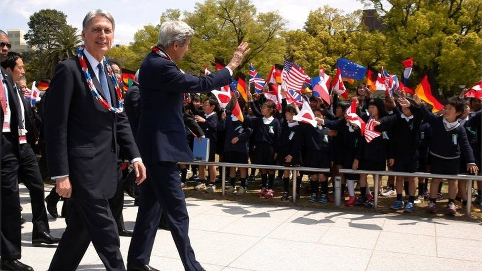 UK Foreign Minister Philip Hammond and US Secretary of State John Key wave at school children at Hiroshima
