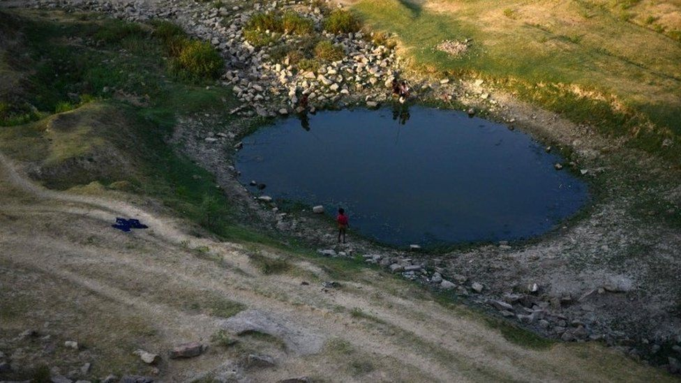 Indian villagers try to catch fish in a pool of the shrunken Mansaita River near Allahabad on May 4, 2016.