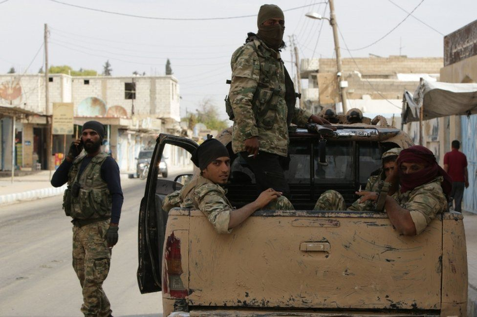 Turkish-backed Syrian fighters sit in the back of a truck in the Syrian border town of Tal Abyad on October 17, 2019