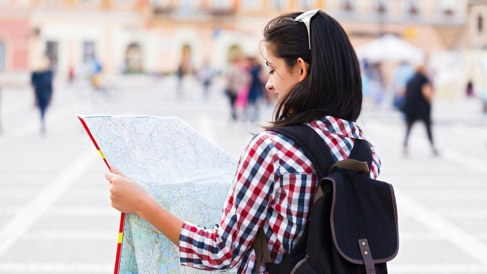 A young woman reading a map in a European city