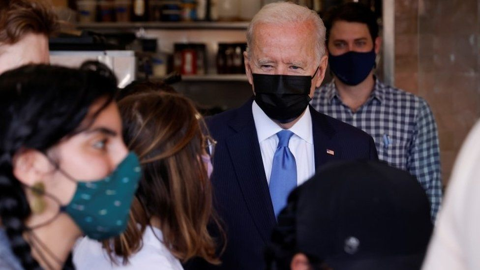Joe Biden speaks with the staff as he visits the Las Gemelas Taqueria restaurant for carry-out lunch on Cinco de Mayo in the Union Market neighbourhood in Washington,