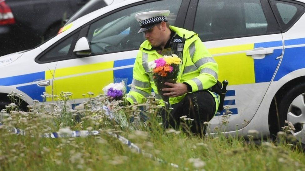 A police officer lays flowers at the scene where PC Andrew Harper was killed