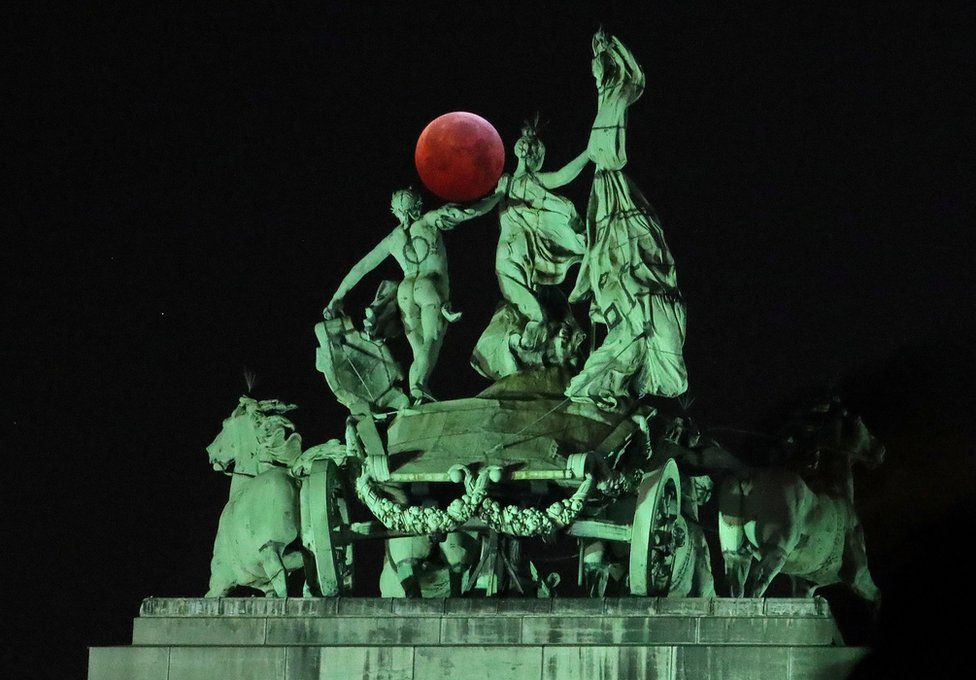 The moon seen beside a quadriga on top of the Cinquantenaire arch in Brussels