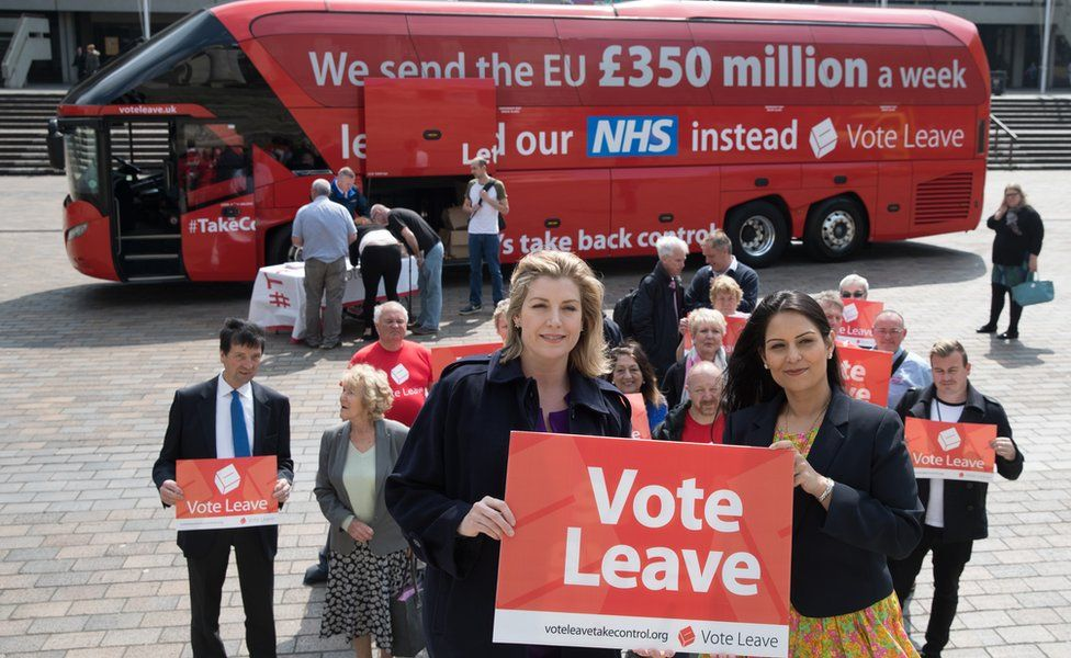 """Vote Leave campaigners with a campaign bus behind them that says """"We sent the EU £350 million a week"""""""