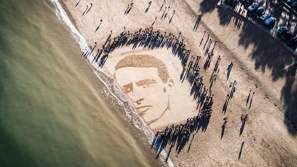 At 11:00, people watched in silence as the tide began washing away the sand portrait of Hedd Wyn