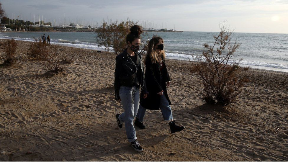 People wearing protective face masks walk on a beach during an unusual warm day in Athens