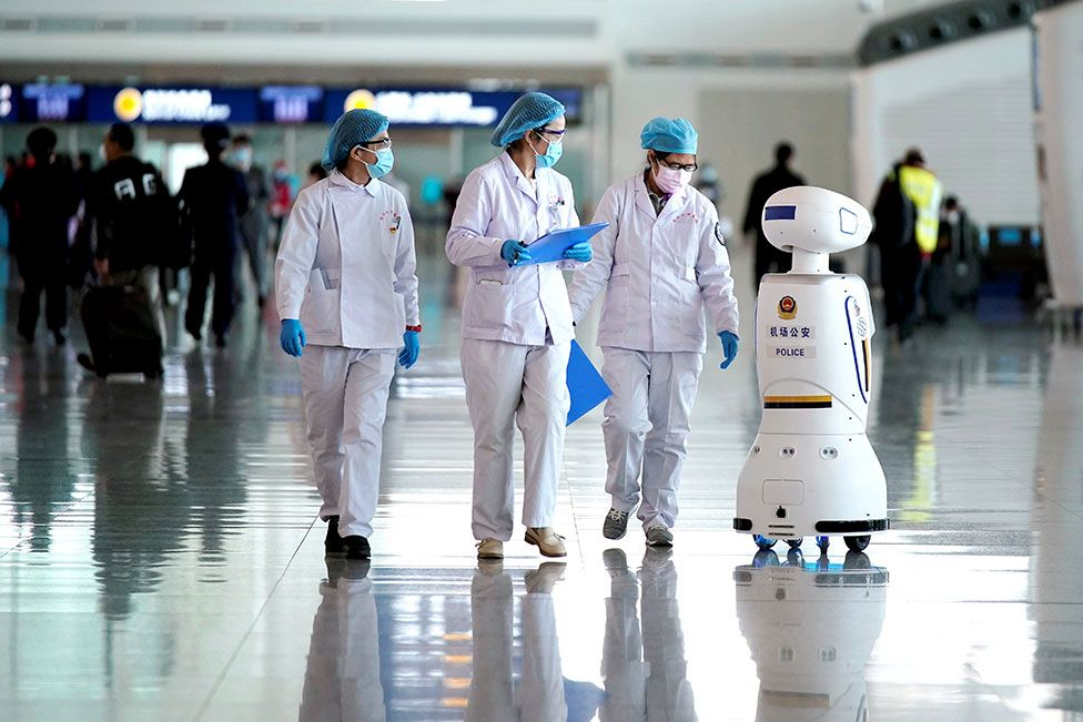 Medical workers walk past a police robot