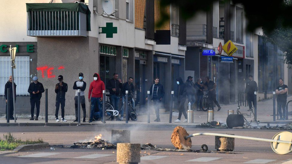 People stand on a damaged street in Dijon on Monday