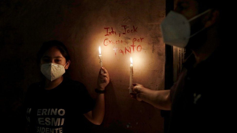 """Women hold candles next to the names of two people who were killed in clashes during protests following the ouster of President Martin Vizcarra, in Lima, Peru November 15, 2020. The writing reads """"Inti, Jack, thank you for so much"""""""