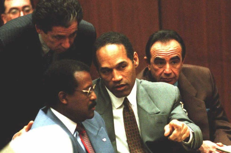 Johnnie Cochran, OJ Simpson and Robert Shapiro sitting in court with Robert Kardashian leaning over them