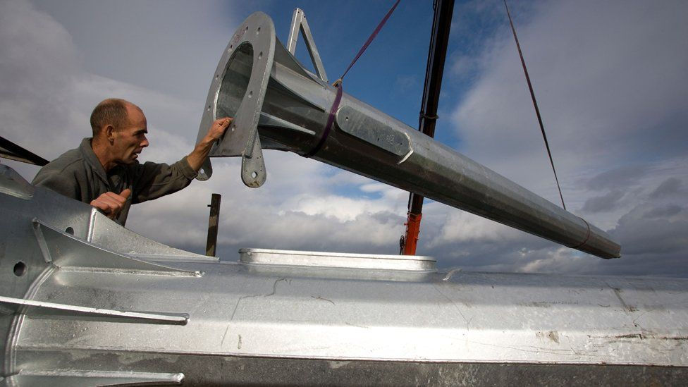 Wind turbine parts are unloaded from the landing craft at the quayside, Eigg