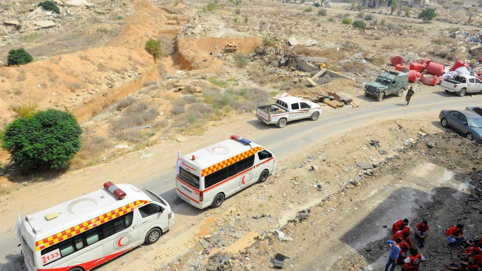 A Syrian Arab Red Crescent convoy waits at the entrance of the besieged Damascus suburb of Darayya.