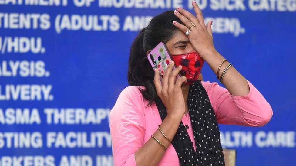A woman on the phone outside a hospital